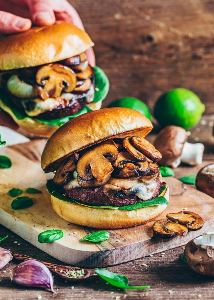 vegane Burgerpatties aus Champignons mit veganem Mozzarella und Spinat, lecker Gericht des Tages, Burger auf einer hölzernen Platte