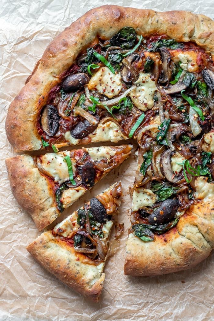 selbstgemachte vegane Pizza mit Champignons und Gemüse und veganem Mozzarella, vegane Hauptgerichte für Gäste