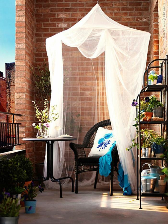 Balkon gestalten Ideen, Design mit weißem Baldachin, weißer Kissen mit blauen Motiven, großer Pflanzenständer