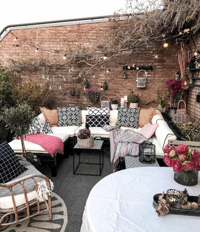 Backsteinmauer mit Kletterpflanzem und Hängeläuchter, großer Ecksofa mit vielen Kissen, dunkel pinke Blumen, Balkon gestalten Ideen