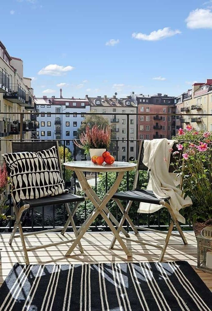 Möbel für kleinen Balkon, schwarzer Teppich mit weißen Streifen, runder Tisch mit zwei Stühlen,