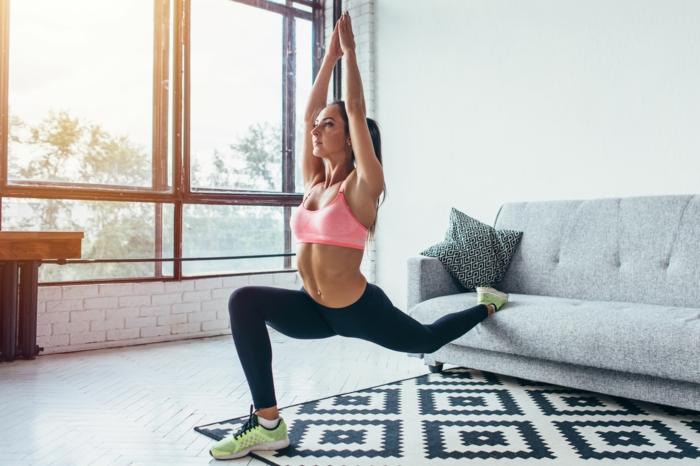Frau in schwarze Legging und pinker Sport BH macht Sport zuhause ohne Geräte, schwarz weißer Teppich, grauer Sofa, kraftübungen ohne Geräte