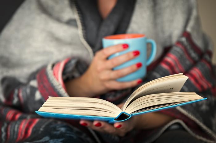 eine frau mit händen mit einem roten nagellack, bücher lesen, eine frau mit einer blauen tasse und mit einem buch