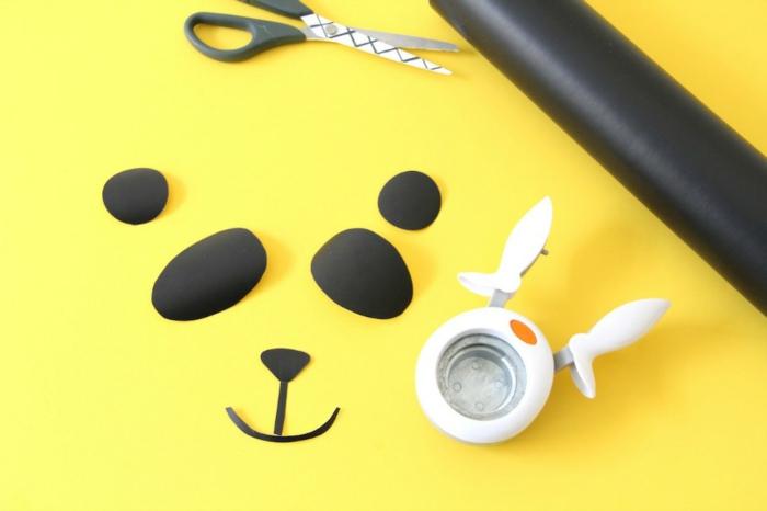 Ausgeschnittene Augen Nase und Mund, wie kann man sich Panda Masken basteln, schwarze Schere