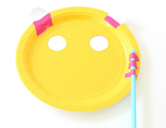 Aufgeklebter Strohhalm auf einem gelben Pappteller, wie kann man sich Panda Masken basteln