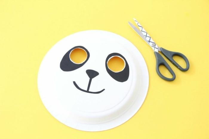Wie kann man sich Panda Masken basteln, fertige Maske, gelber Hintergrund, schwarze Schere