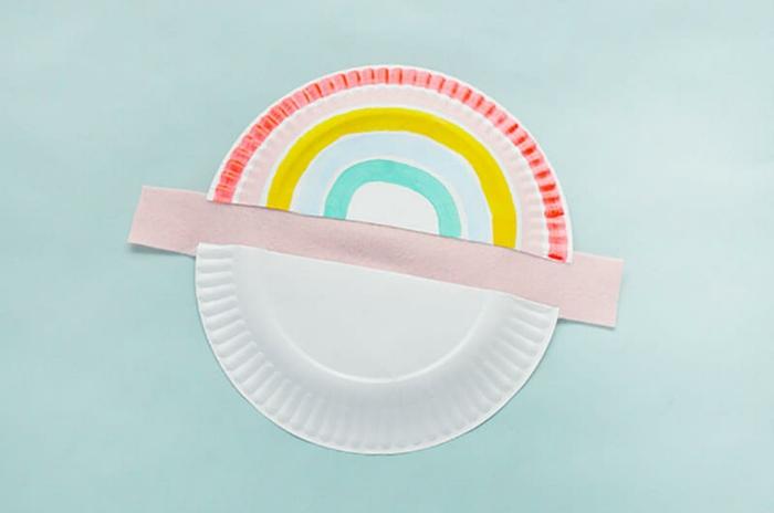 Regenbogen basteln DIY Anleitung, aufgeschnittener Pappteller in zwei, Hälfte bemalt in bunten Farben