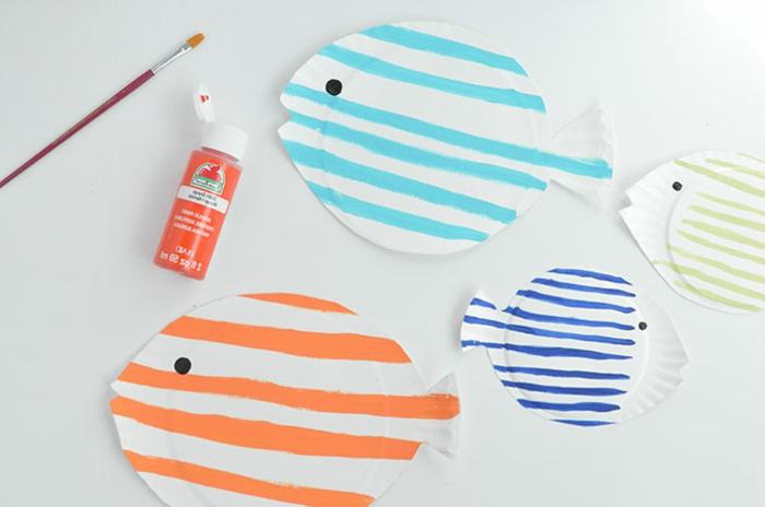 vier bemalte in verschiedene Farben Fische aus Pappteller, Unterwasserwelt basteln, Tube mit roter Farbe