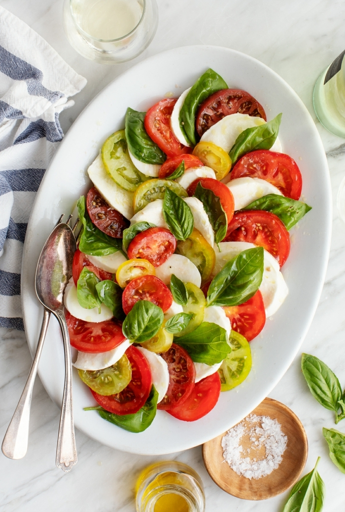 leckere salate, capresesalat mit roten und gelben cherry tomaten garniert mit basilikum und mozzarella