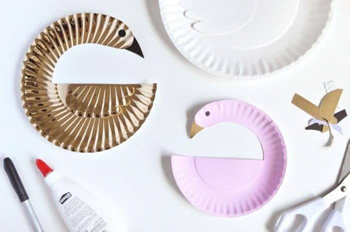 zwei goldene und pinke Schwäne, eine weiße Schere und ein schwarzer Stift, Tiere aus Pappteller basteln