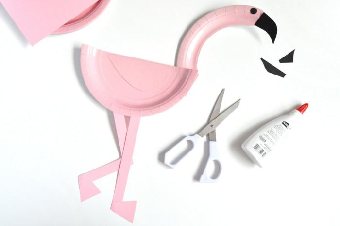 gebastelter pinker Flamingo, Klebstoff und weiße Schere, Tiere aus Pappteller basteln DIY