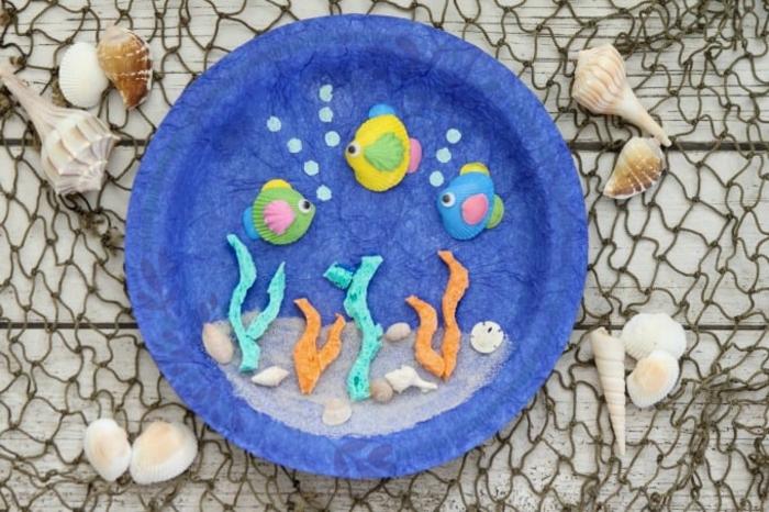 Aquarium basteln, drei Fische aus Muscheln, bemalt in gelb, grün und blau, Meerespflanzen aus Schwamm