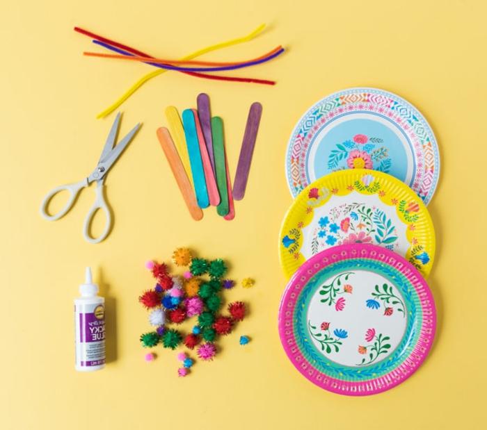 Bastelbedarf zum Schmetterlinge basteln mit Kindern, drei bunte Pappteller und bunte Pompons