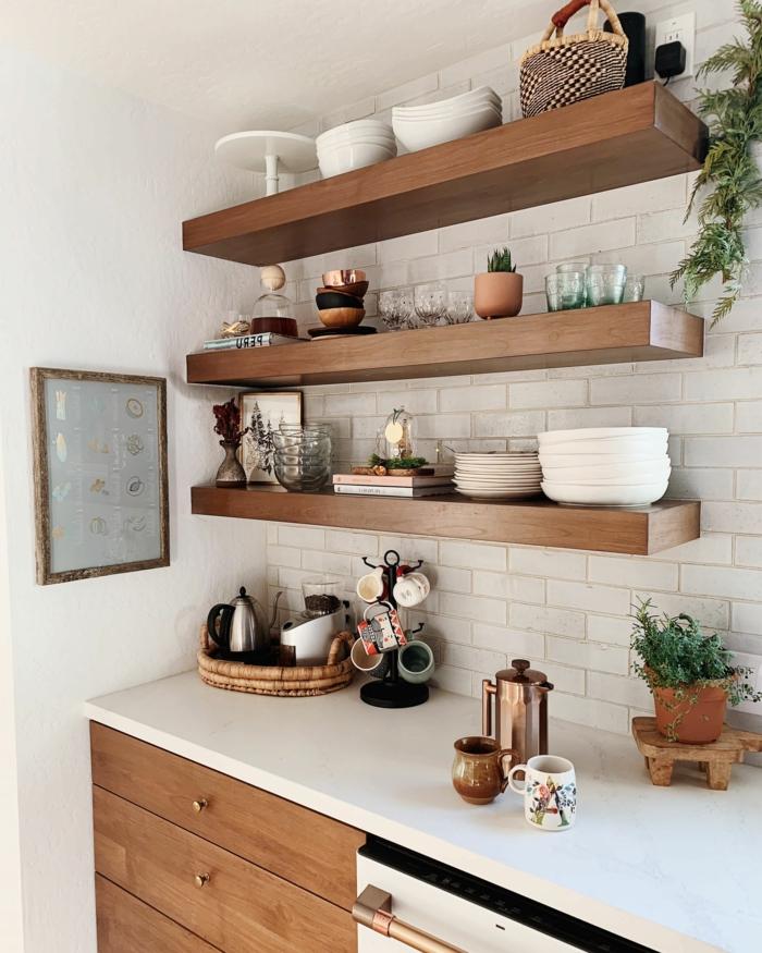 kleine moderne Küche, offene Regale aus Holz mit Tellern und Tassen, weiße Fliesen, minimalistisches Design