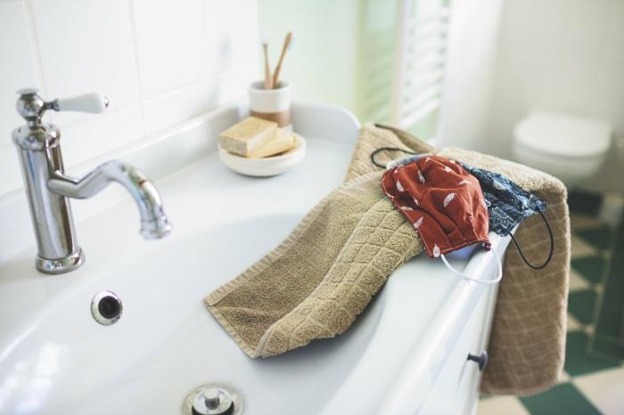 tuch und zwei schutzmasken gegen viren und bakterien, badezimmer und zwei community masken, eine rote und eine blaue maske, mundschutz reinigen