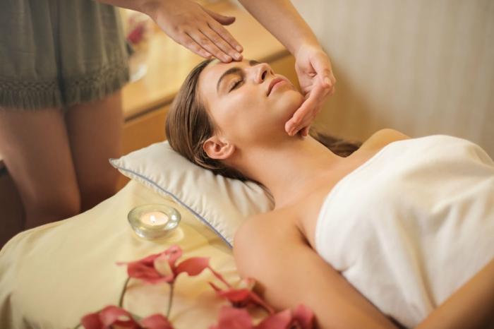 Massage und Hautpflege, kosmetische Dermatologie, Frau liegt auf einem Bett und lässt sich massieren, Laser Haarentfernung