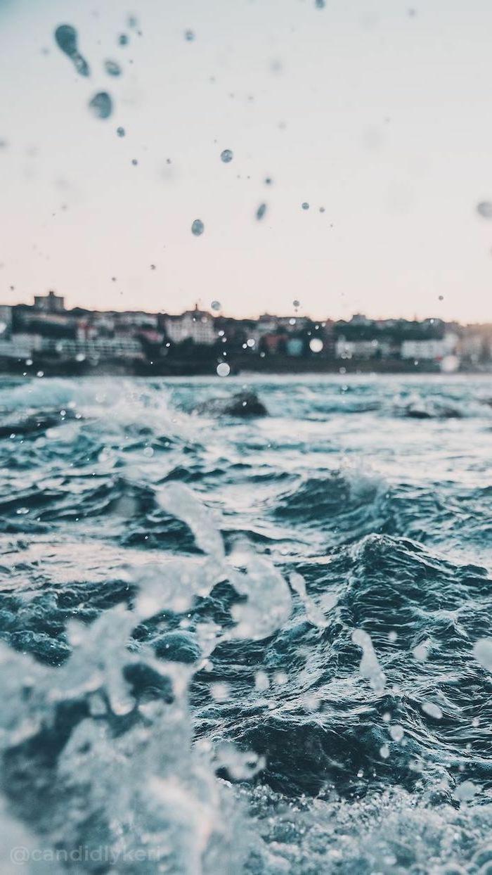 Nahaufnahme von Wellen, Küste und Häuser im Hintergrund. aesthetic iphone wallpaper