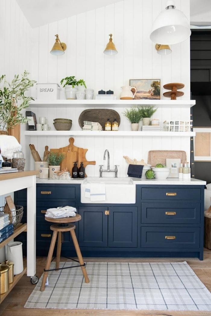 Moderner blauer Küchenschrank, offene Regale mit Küchenutensilien, drei goldenfarbige Lampen, kleine Wohnküche Ideen