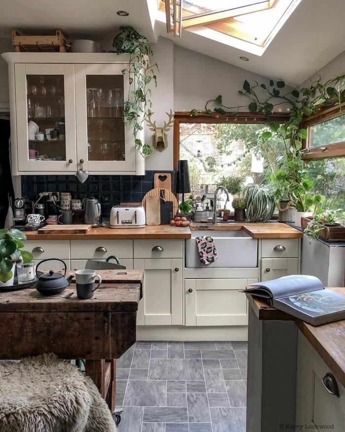 Küchenlösung für kleine Küchen mit Tisch aus Holz, Einrichtung im bohemischen Stil, weiße Schränke und große Fenster