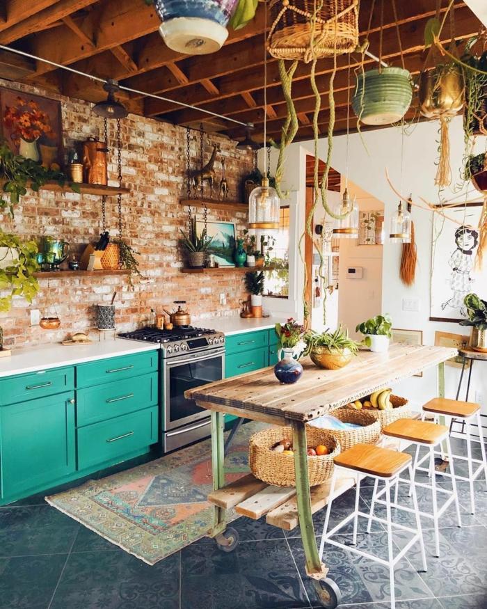 großer Tisch aus Holz mit drei Barstühle, Ziegelwand mit aufgehängten Regalen, Schränke in Türkis, Dekoration mit vielen Pflanzen, Designer Küchen