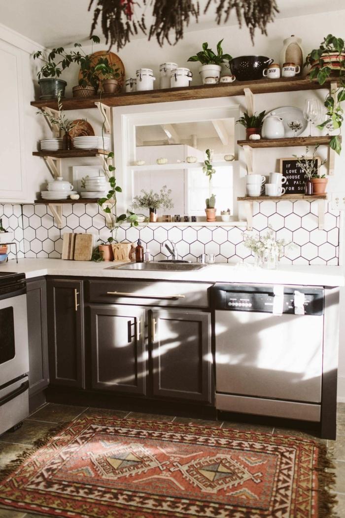 weiße Fliesen in sechseckiger Form, viele grüne Pflanzen als Dekoration, bunter Teppich, offene Regale mit Küchenutensilien, Küche weiß Holz,