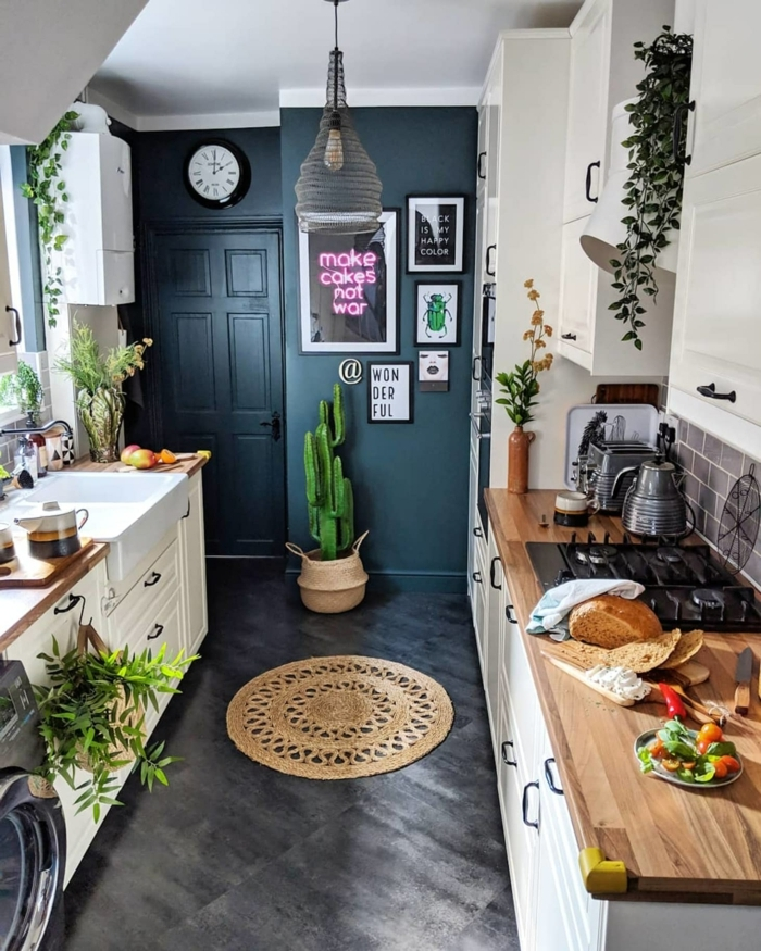 blaue Wand mit aufgehängten Bilder, großer grüner Kaktus, Arbeitsplatte aus Holz, Küchen Inspiration