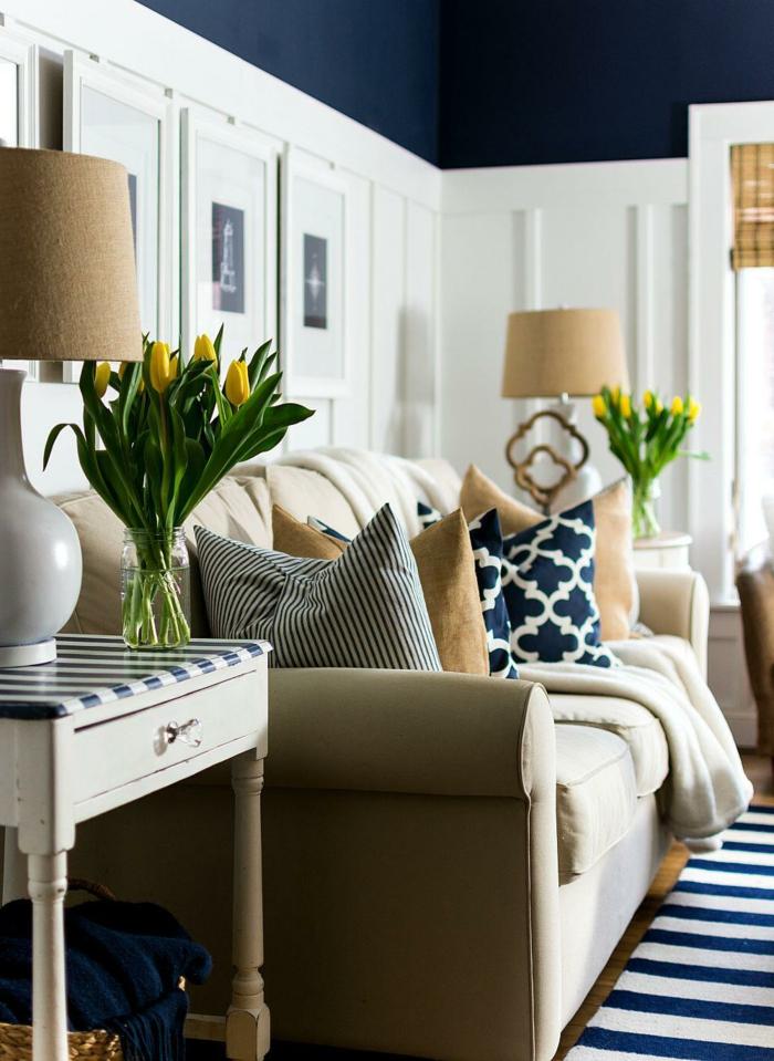 viele gelbe Tulpen, blau weißer Teppich, beiger Couch mit vielen bunten Kissen, Frühlingsdeko aus Naturmaterialien selber machen
