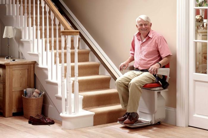 ein alter mann mit weißem haar und rotem hemd und braunen schuhen, ein zimmer mit treppen und einem boden aus holz und treppenlift