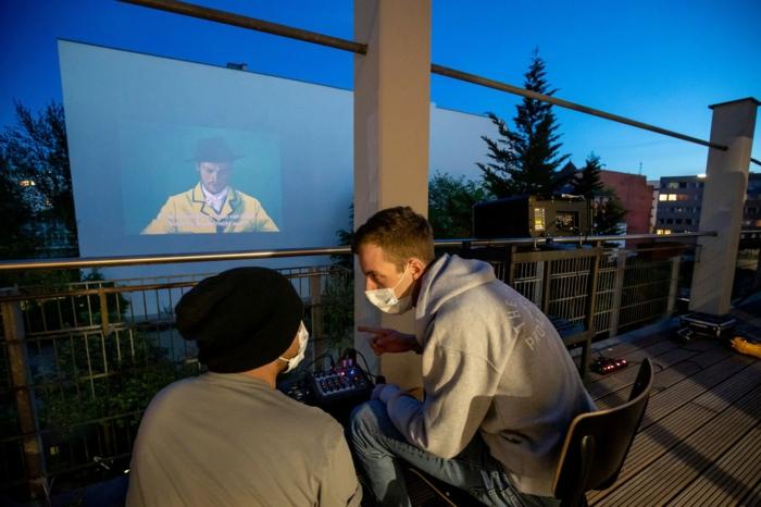 ein mann mit hut, zwei männer mit weißen schutzmasken gegen viren, kino in berliner hiterhöfe, loving vincent