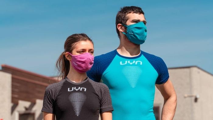mundschutz reinigen, eine junge frau mit einer violetten maske, ein mann mit einem blauen t-shirt und einer blauen community maske gegen viren und bakterien