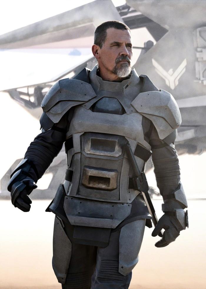 der schauspieler josh brolin in einer szene aus dem sci fi film dune von dem regisseur denis villeneuve, ein mann mit bart in wüste, ein raumschiff