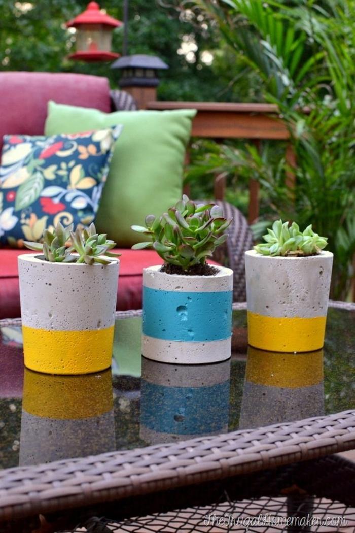 Beton Blumentopf in blau und gelb, Dekoration für den Garten, Blumenkübel selber machen, rosa Sofa mit bunten Kissen