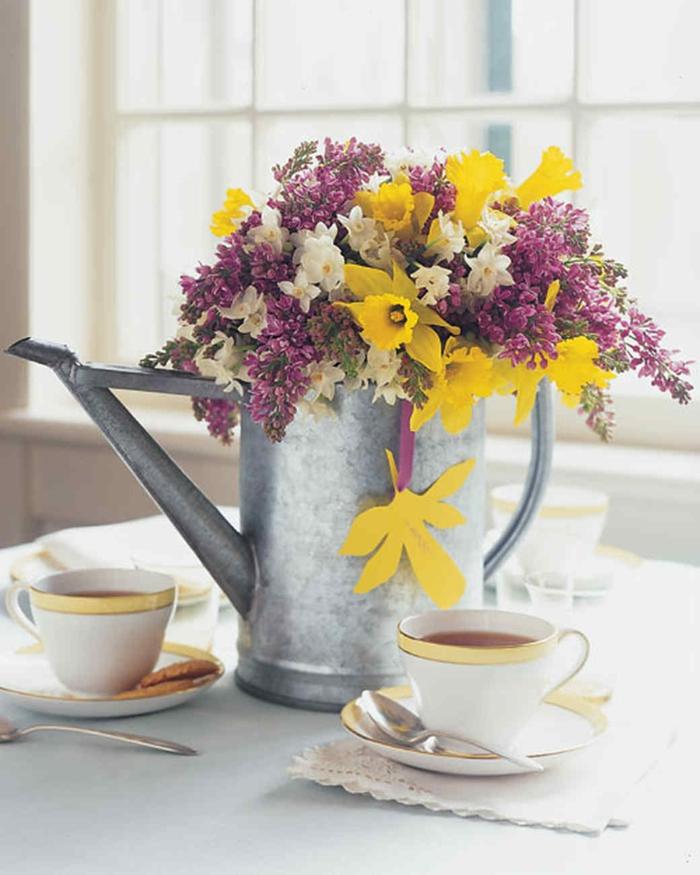 Frühlingsdeko basteln mit Naturmaterialien, gelbe weiß und lila Blumen in einer Gießkanne aus Metall