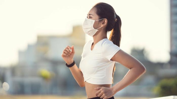 Frau mit braunen Haaren joggt draußen und trägt eine Atemschutzmaske, wie schütze ich mich vor Viren