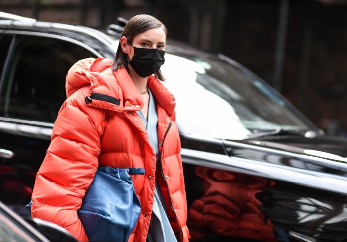 Frau angezogen in große orange Jacke und schwarze Gesichtsmaske, blaue Tasche, Coronavirus Schutz