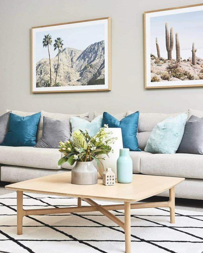 Deko für die Wohnung mit blauen Tönen, großes graues Sofa mit vielen Kissen, zwei Bilder an die Wand