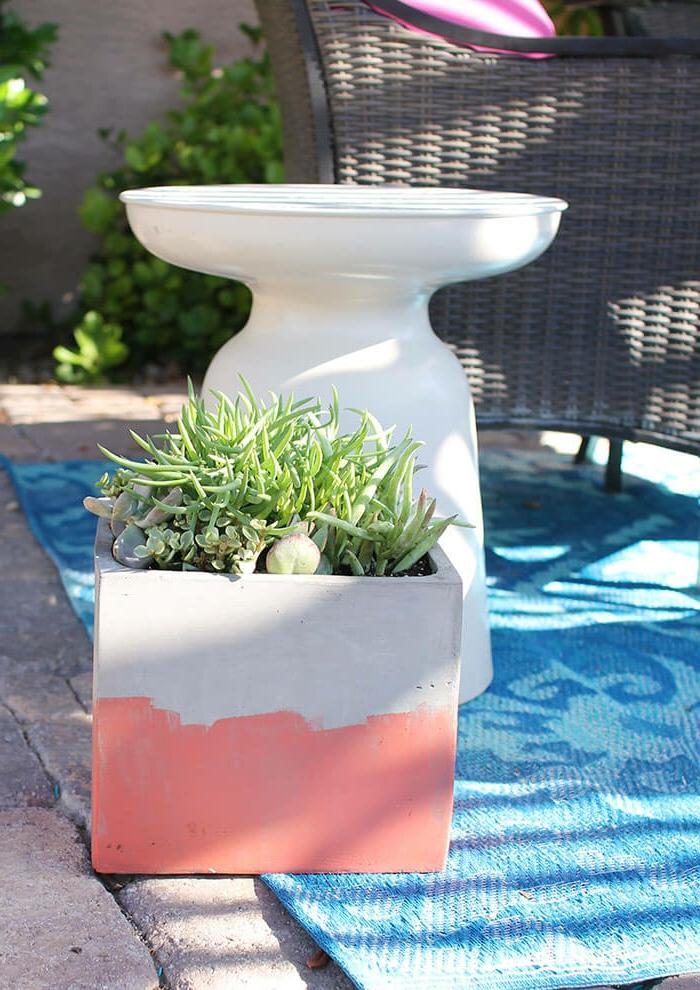 Dekoration für den Garten selber machen, Beton Blumentopf in pink und grau, Betonkübel für Pflanzen, blauer Teppich