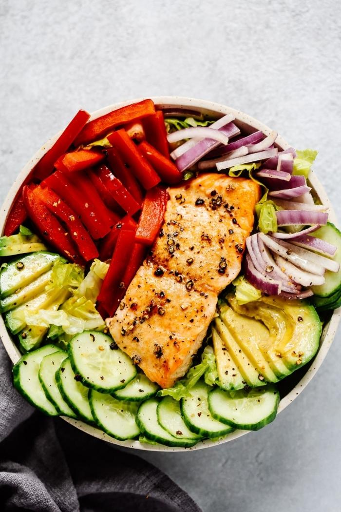 gemischter salat mit fisch, lachs mit rotem paprika, gurken, avocado und zwiebel