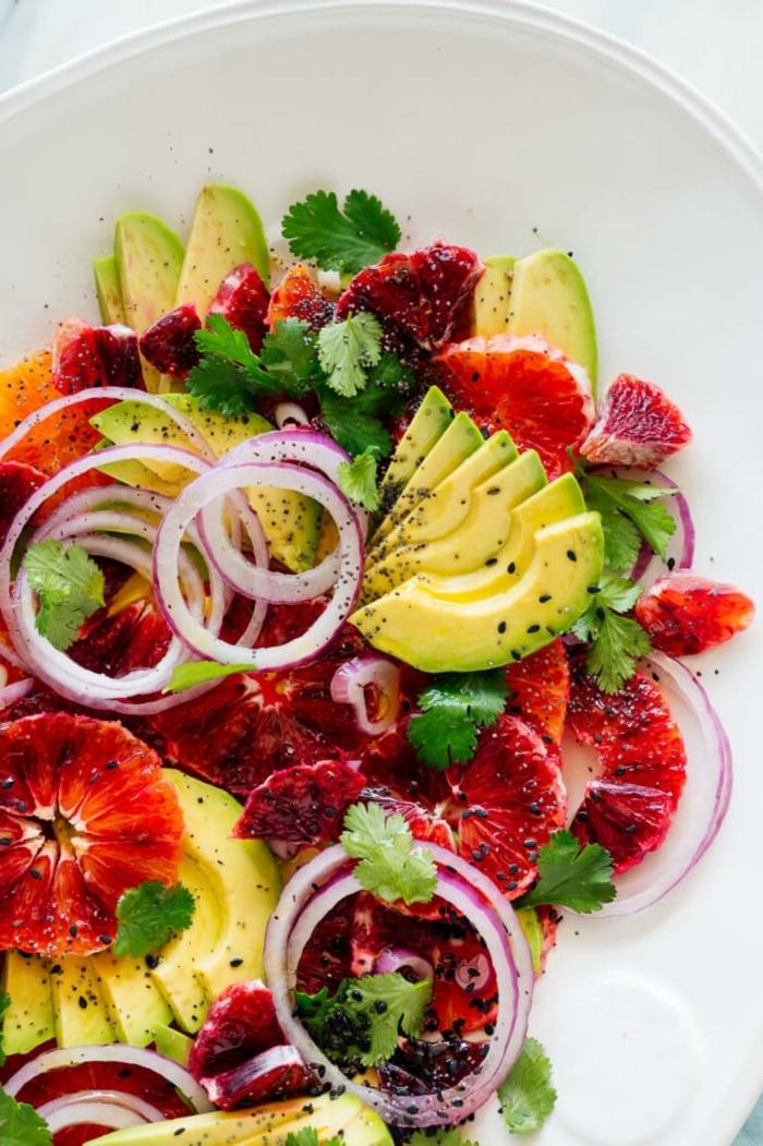gemischter salat mit roter orange und avocado garniert mit zwiebel und gehakter petersilie