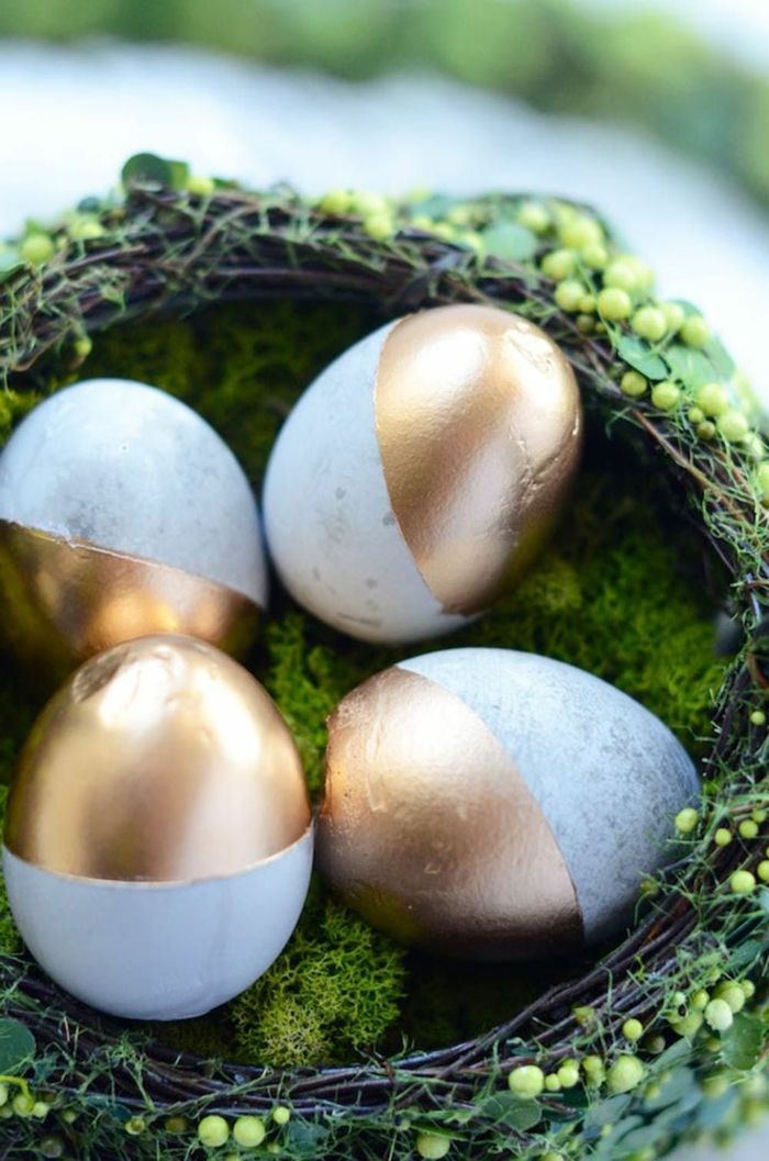 vier Eier bemalt in grau und goldenen Farbe in einem Nest, Gefäße aus Beton selber machen,