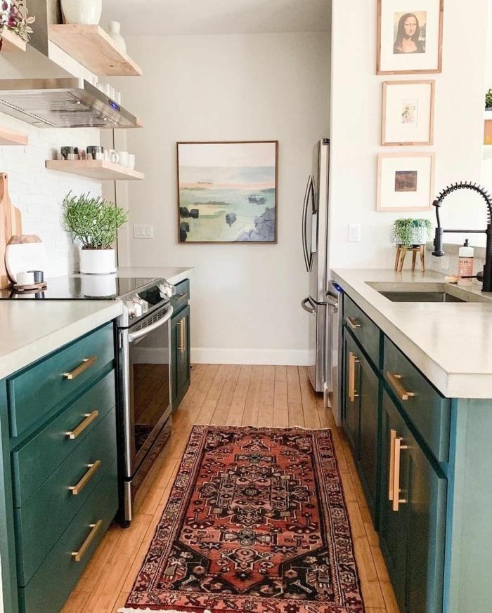 kleine moderne Küche mit grünen Schränken, bunter Teppich auf Holzboden, Bilder an die Wand