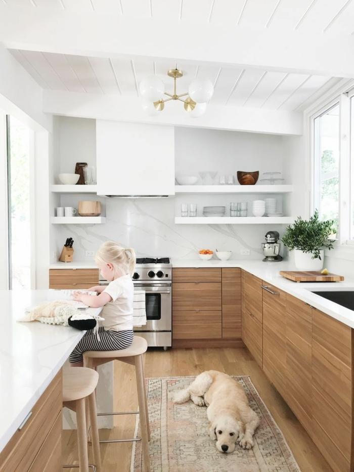 Küche weiß Holz, Regale mit Tassen und Tellern, kleines Mädchen sitzt auf eine Kücheninsel, Hund liegt auf einem bunten Teppich,