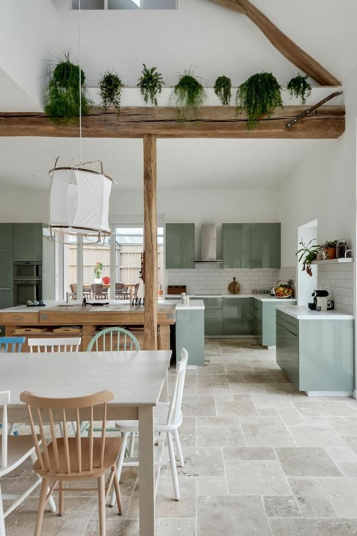 große Küche mit offenem Essbereich, weißer Esstisch mit verschiedenen Stühlen, Hohe Decke mit Holzbalcken, Küche l Form mit Fenster