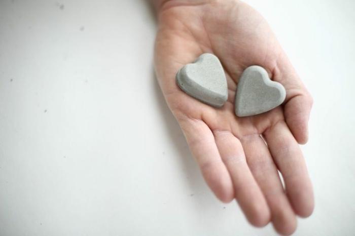 zwei kleine Herzen aus Beton in eine Hand, Betonarbeiten selber machen, kreative DIY Ideen
