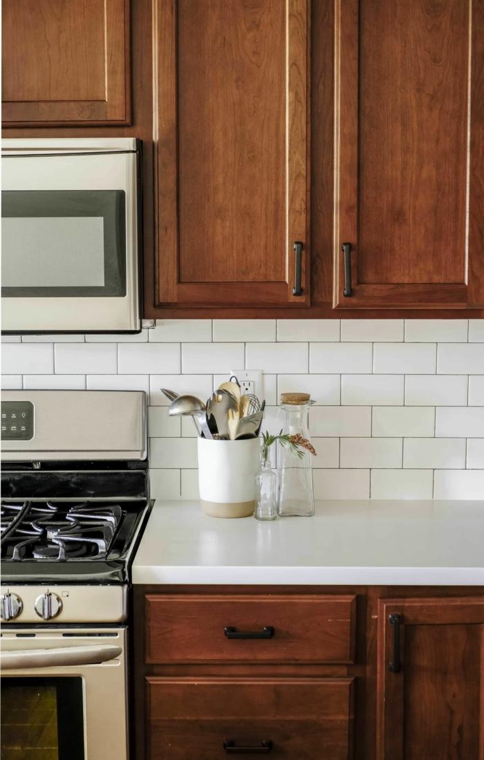 kleine Wohnküche Ideen, Küchenschränke aus Holz, weiße Arbeitsplatte, leere Glasflasche,