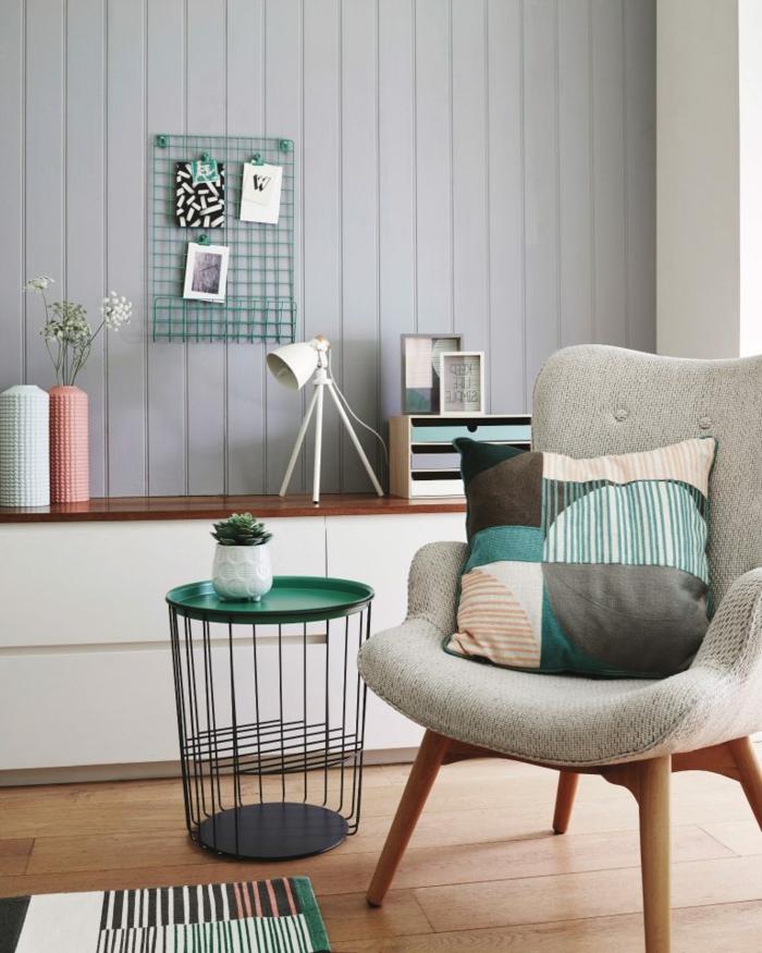 Pinterest Wohnzimmer modern einrichten, bunter Kissen auf einem grauen Stuhl, grüner Korbtisch, grau bemalte Wand