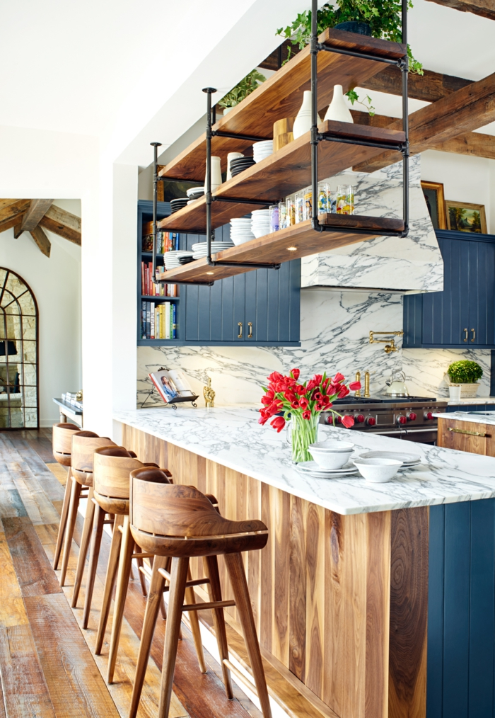hängendes Regal mit Tassen und Tellern, blaue Schränke und Theke aus Holz und Marmor, Designer Küchen