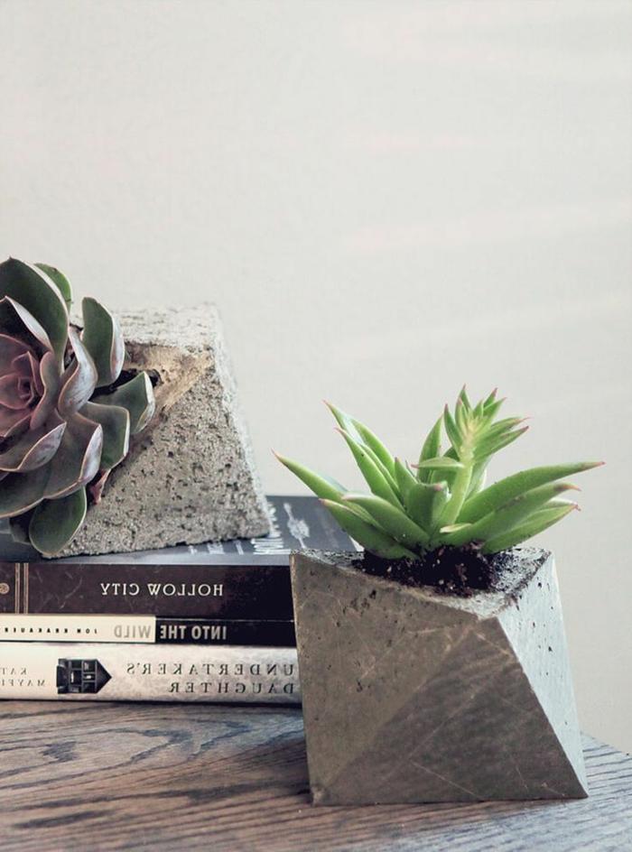 drei aufeinander gelegte Bücher, zwei Pflanzer aus Beton mit Pflanzen, Blumenkübel selber machen