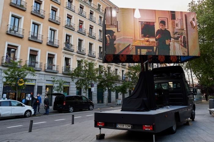 ein mobiles kino in madrid während der coronavirus krise, ein leinwand mit einem film, straße in madrid