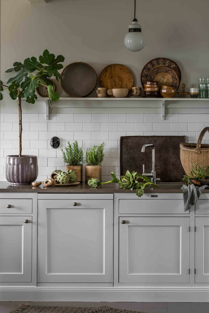 Einrichtung im skandinavischen Stil, Küche modern weiss mit vielen Holztellern, grüne Pflanzen